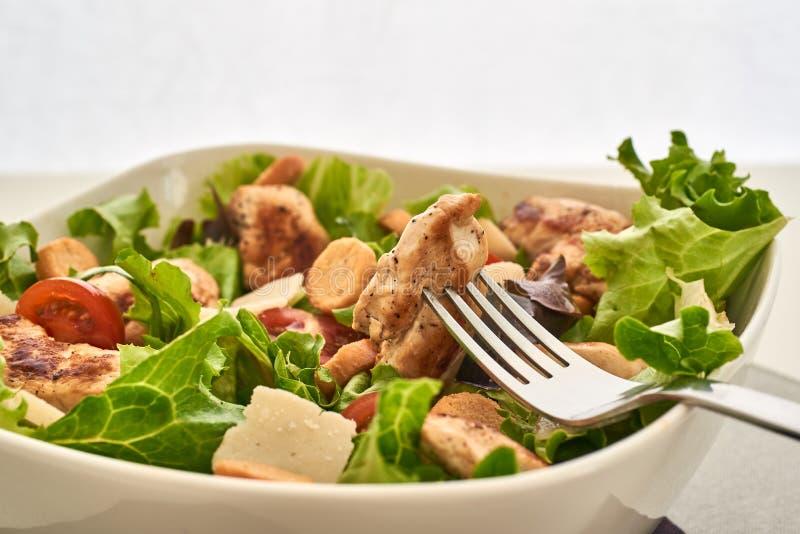 Sluit omhoog op een cesar salade en een brok van kip in een vork royalty-vrije stock afbeelding