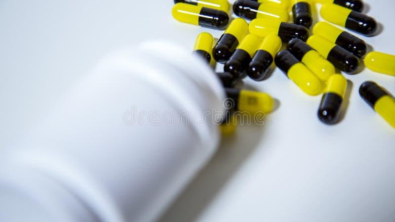Sluit omhoog op een fles van voorschriftdrugs die uitvallen Zwarte en gele pillen stock afbeeldingen