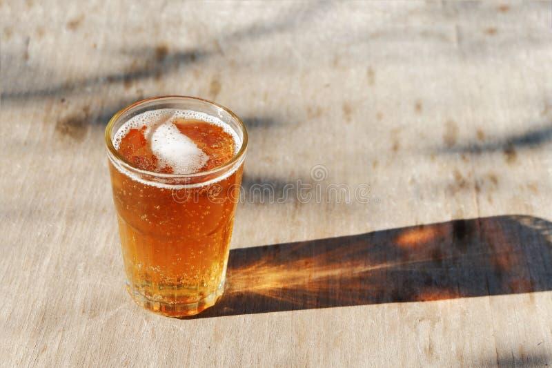 Sluit omhoog op een pintglas amberpale ale-bier, die een schaduw op een oude houten lijst, en ruimte voor tekst gieten stock afbeelding
