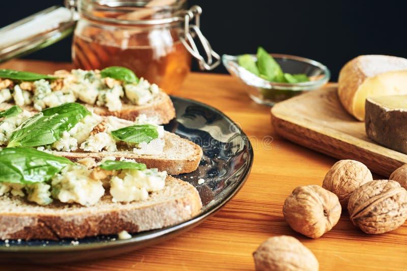 Sluit omhoog op een plaat van toosts met roquefortkaas, okkernoten, honing en basilicum Wat kaas, noten en honing op de achtergro stock fotografie