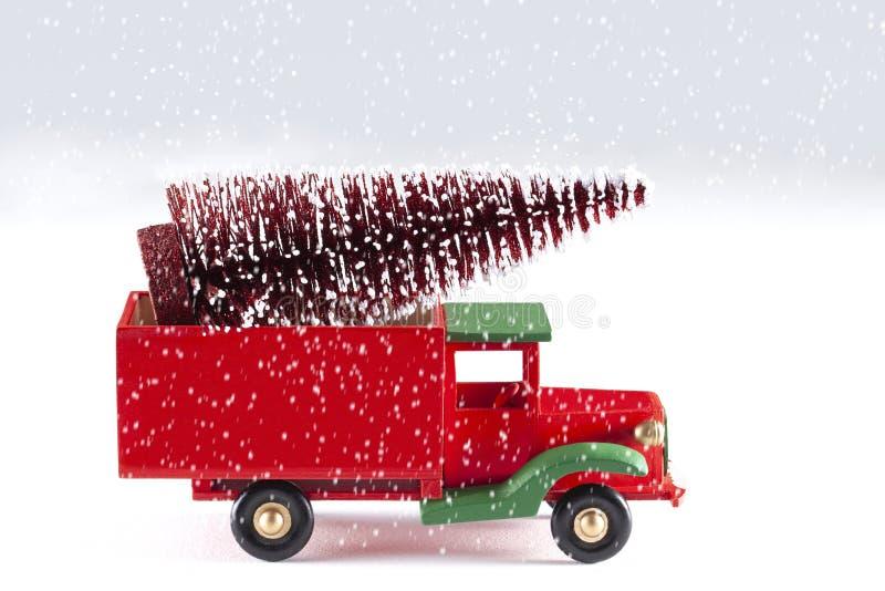 Sluit omhoog op een stuk speelgoed auto met Kerstboom en sneeuwvlokken op witte achtergrond worden geïsoleerd die stock foto