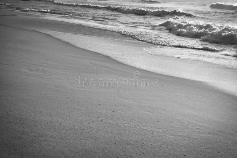 Sluit omhoog op golfschuim van de Atlantische Oceaan op zandig strand in zwart-wit royalty-vrije stock foto