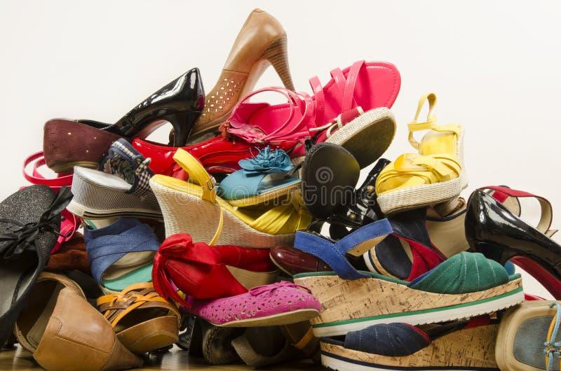 Sluit omhoog op grote stapel van kleurrijke vrouwenschoenen stock afbeelding