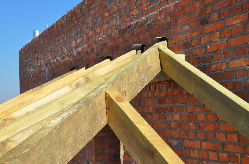 Sluit omhoog op houten daksparren, eaves, worden geïnstalleerd verankert de houten die stralen op bakstenen muur met bitumen wate stock foto