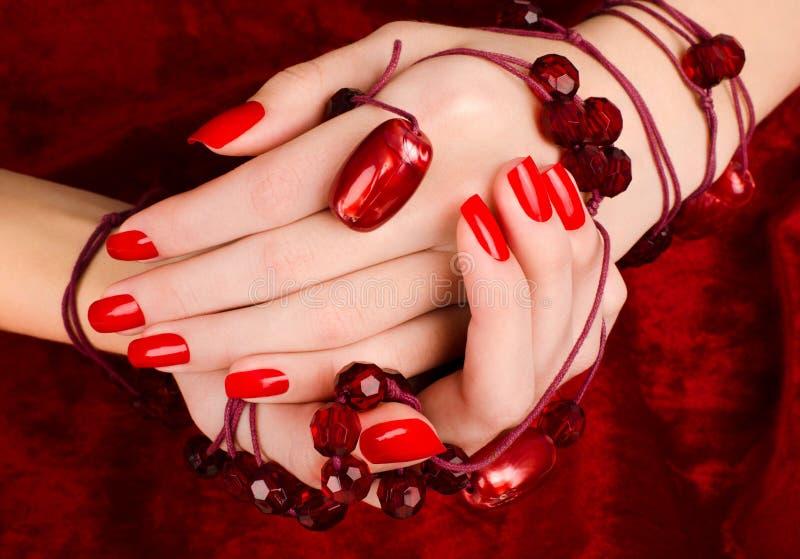 Sluit omhoog op mooie vrouwelijke handen met sexy rode manicure. stock foto's