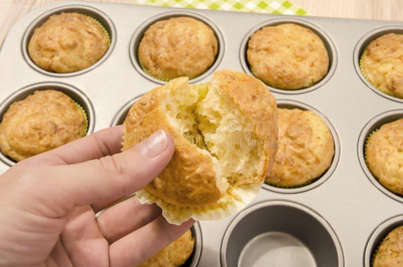 Sluit omhoog op muffins in een dienblad en vrouwenhand die een gesneden geopende muffin tonen royalty-vrije stock fotografie