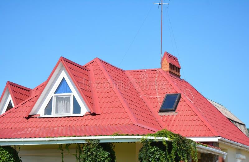 Sluit omhoog op rood metaaldak met mansard, dakraamvenster, systeem van de dak het guttering pijpleiding royalty-vrije stock foto