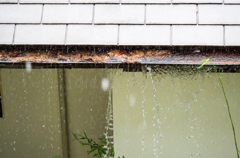 Sluit omhoog op sectie van dakgoot die met bladeren, puin op woonhuis tijdens de regen wordt belemmerd stock foto