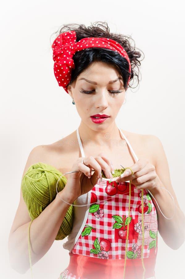 Sluit omhoog op sexy jonge donkerbruine dame die pret hebben die schort en rode boog dragen en het breien doen stock afbeeldingen