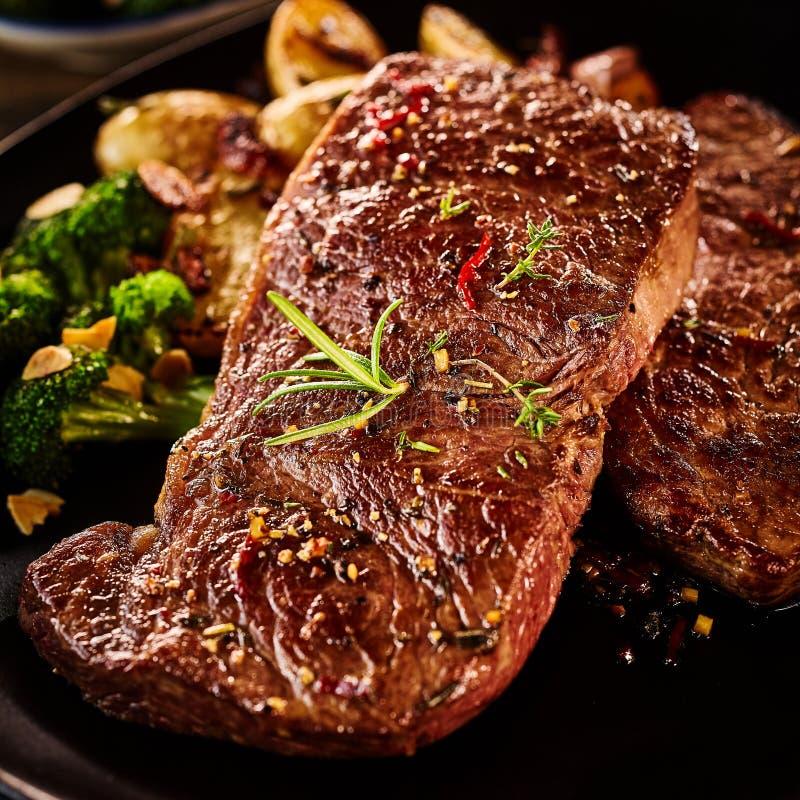 Sluit omhoog op stuk van gemarineerd rundvlees met rozemarijn stock foto
