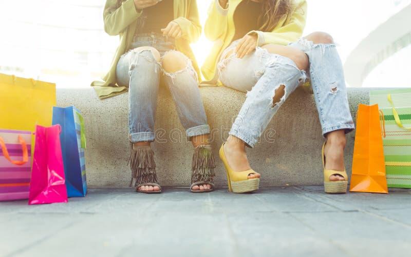 Sluit omhoog op twee meisjes met het winkelen zakken royalty-vrije stock fotografie