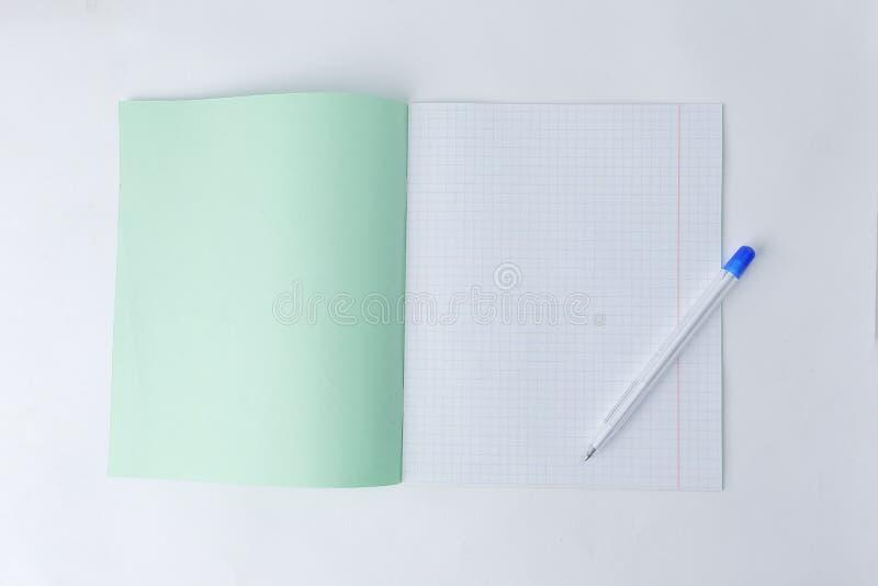 Sluit omhoog open schoolnotitieboekje in een kooi en een ballpoint Foto met exemplaarruimte stock foto