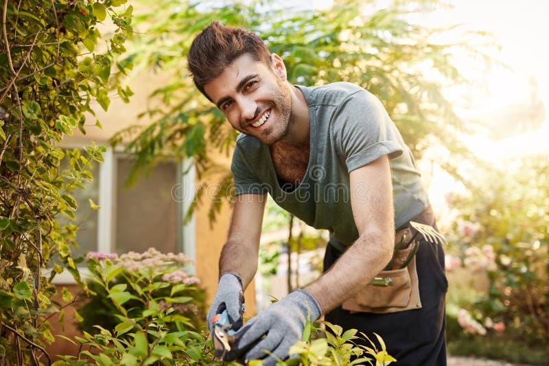 Sluit omhoog in openlucht portret van mooie vrolijke gebaarde Kaukasische landbouwer in blauw overhemd en handschoenen in camera  stock afbeelding