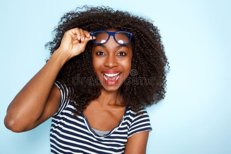 Sluit omhoog opgewekte jonge Afrikaanse Amerikaanse vrouw met krullend haar die glazen op blauwe achtergrond dragen stock afbeeldingen