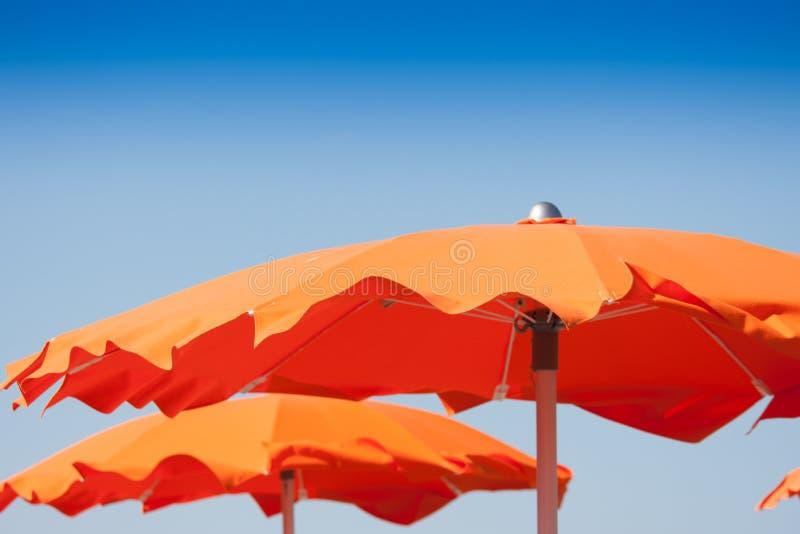 Sluit omhoog oranje paraplu's in strand, Italië royalty-vrije stock afbeelding