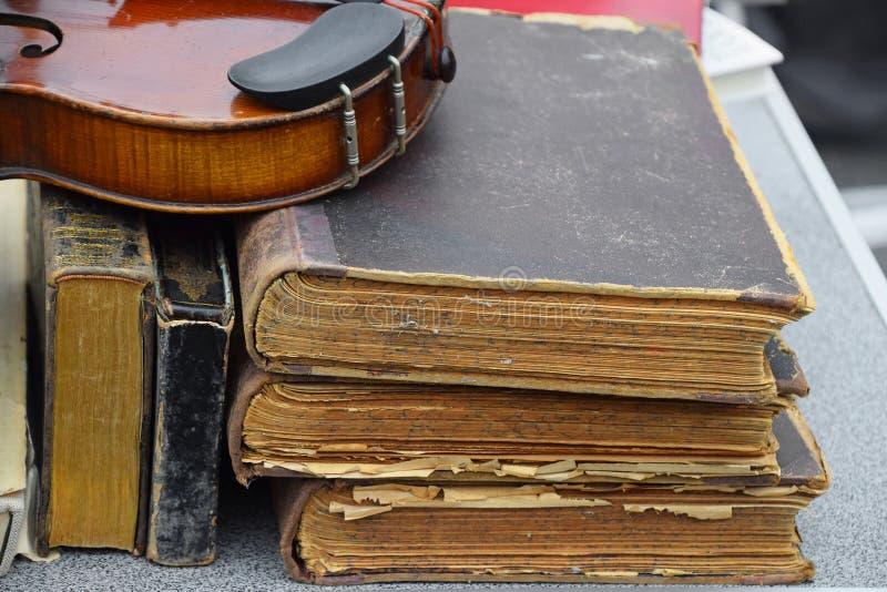 Sluit omhoog oude uitstekende antieke viool en boeken stock afbeelding