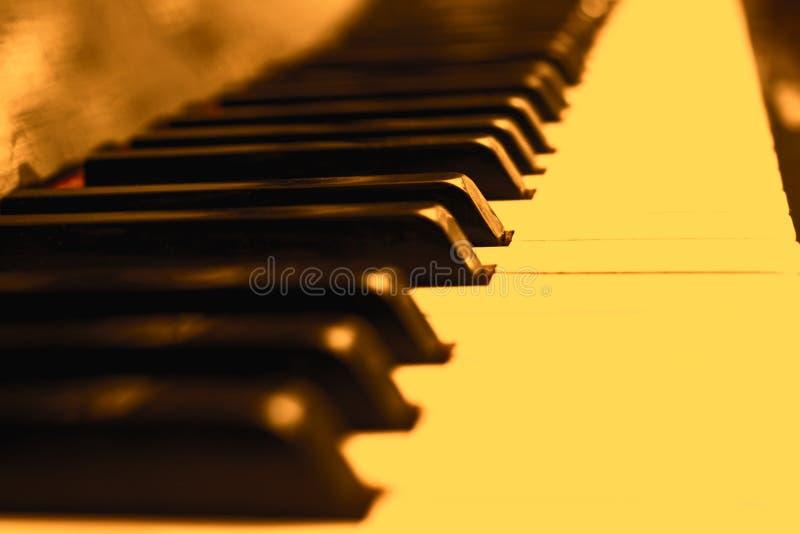 Sluit omhoog pianosleutels in weinig gele sepia stock fotografie