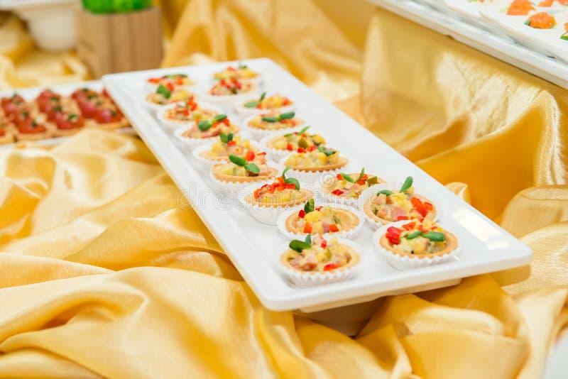 Sluit omhoog plaat met tartalets op cateringslijst met schotels en snacks op de bedrijfsgebeurtenis in de hotelzaal De dienst bij royalty-vrije stock afbeelding