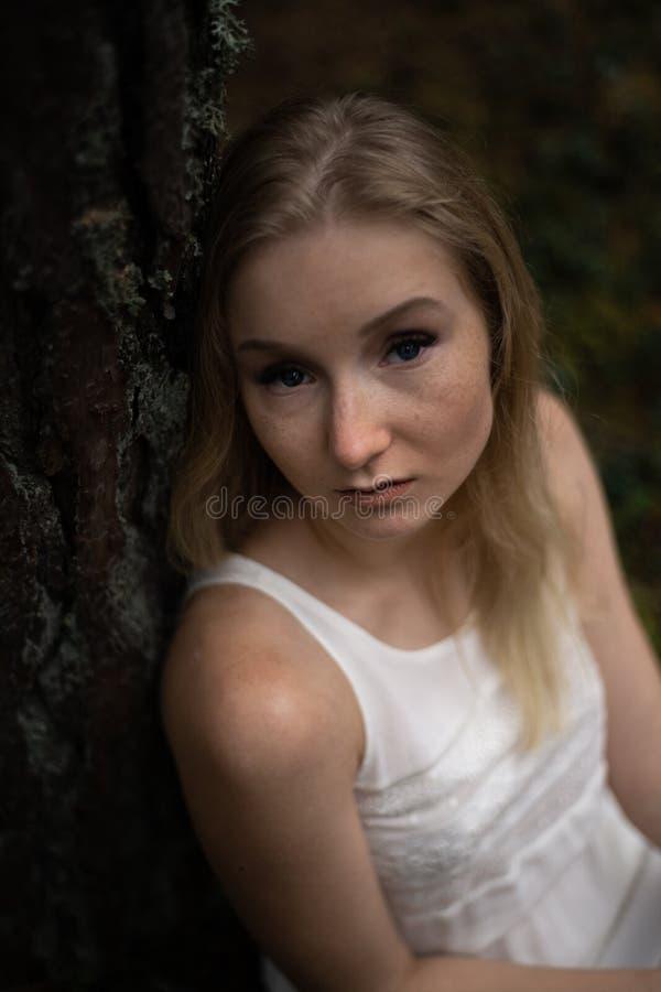 Sluit omhoog portret - de Mooie jonge bosnimf van de blondevrouw in witte kleding in altijdgroen hout stock fotografie