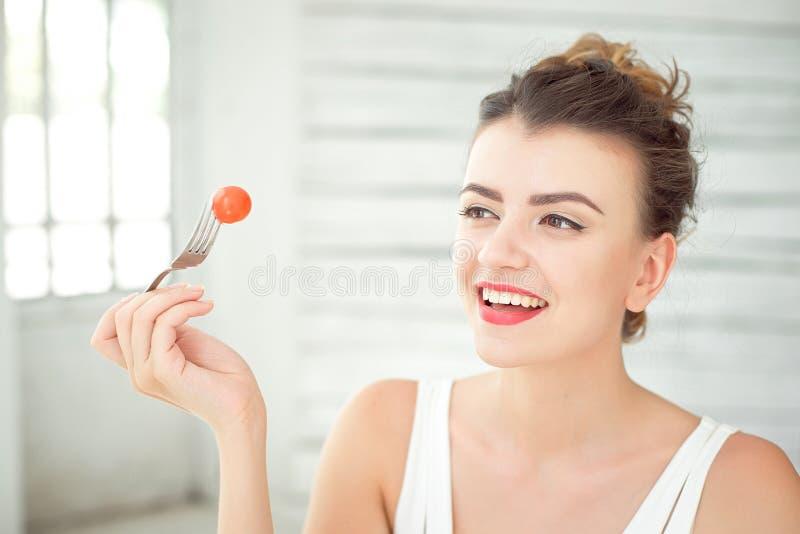 Sluit omhoog portret van aantrekkelijke gezonde jonge vrouw die groene salade binnen eten stock foto's