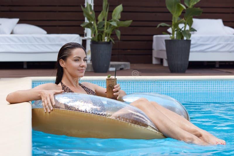 Sluit omhoog portret van aantrekkelijke slanke gelooide vrouwelijke zitting op rubberring dichtbij poolsiderand in blauw duidelij stock foto