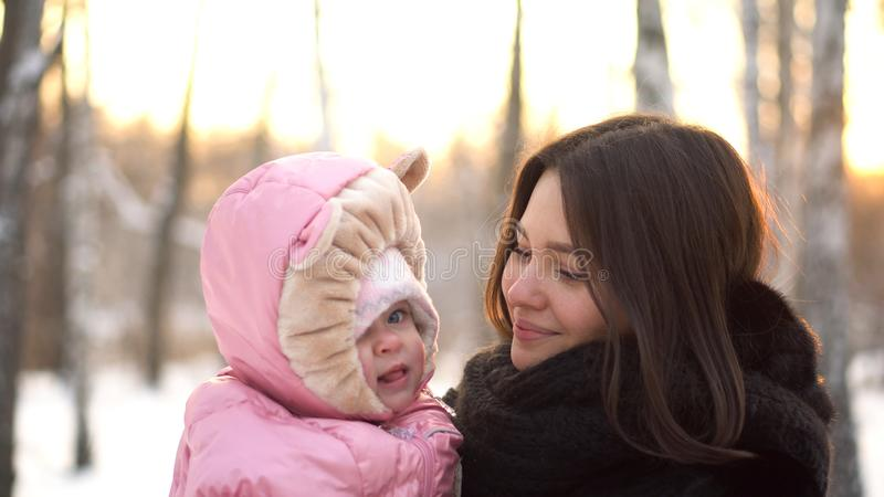 Sluit omhoog portret van baby en haar jonge, mooie moeder buiten bij sneeuwbomen op de achtergrond van het de winterpark Gelukkig stock afbeelding