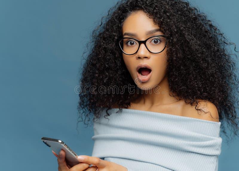 Sluit omhoog portret van bedwelmde jonge vrouw met Afro-kapsel, houdt mond geopend wijd, houdt smartphone, ontvangt het schokken stock foto's