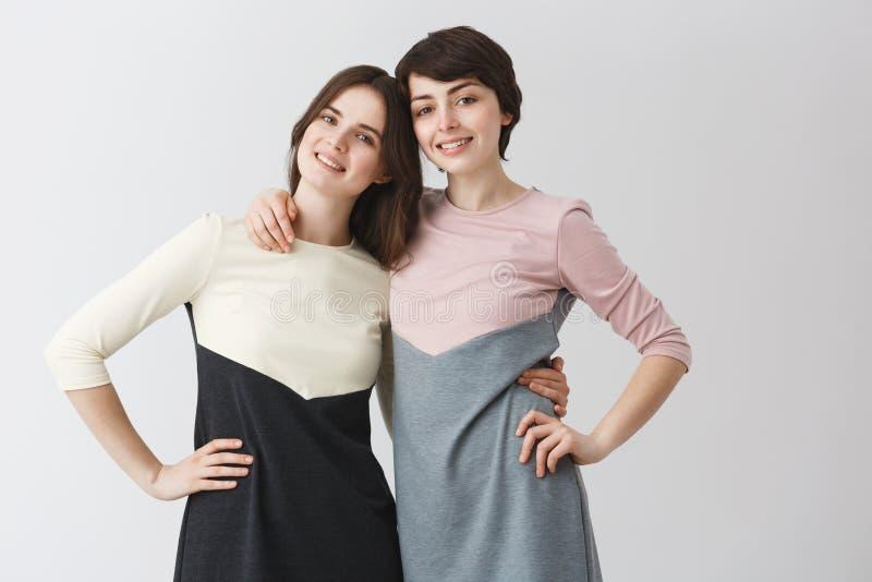 Sluit omhoog portret van blij lesbisch paar die elkaar koesteren, die hand op taille houden, die voor foto in aanpassing stellen stock afbeelding