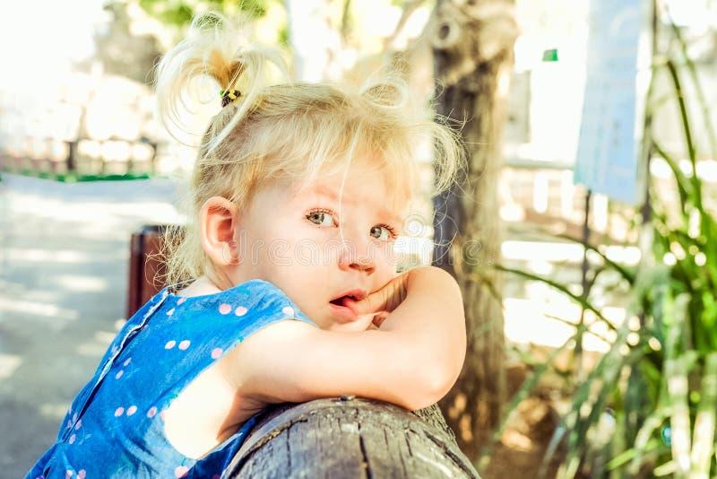 Sluit omhoog portret van bondy peutermeisje met mooie blauwe ogen met scheuren in het park Van kindgevoel en emothions concept zi royalty-vrije stock fotografie