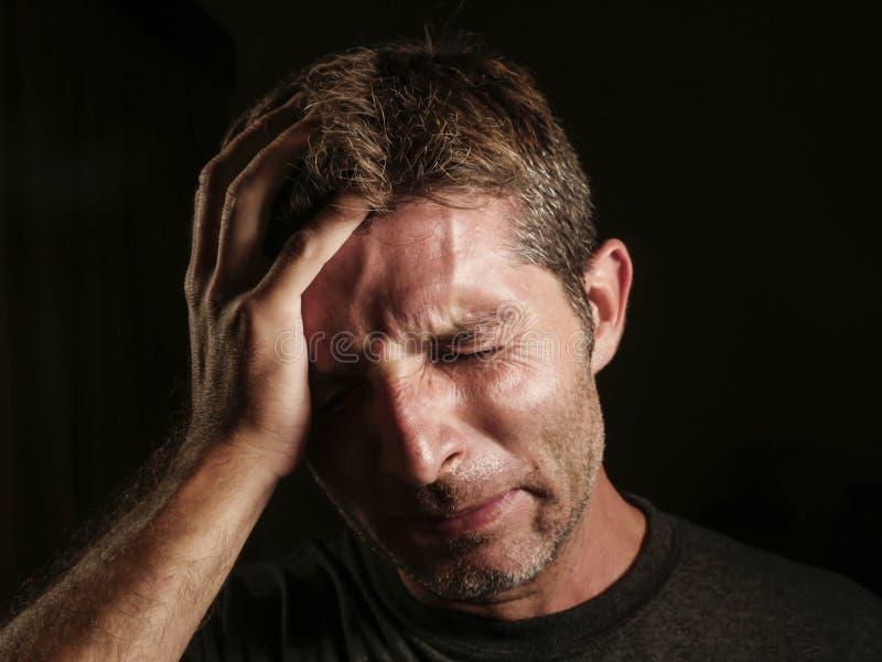 Sluit omhoog portret van de droevige en gedeprimeerde mens die met hand op gezicht wanhopig binnen gefrustreerd gevoel en het hul stock afbeeldingen
