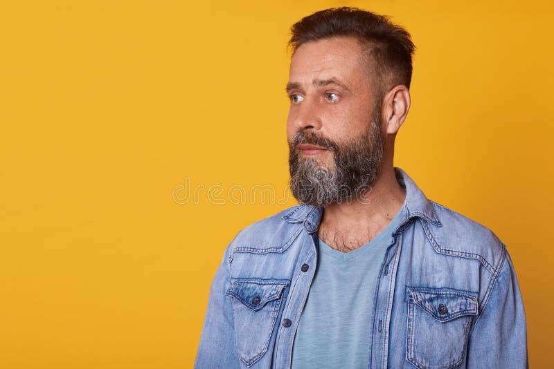 Sluit omhoog portret van de ernstige aandachtige mens die, kalm en peinzend, dragend toevallig jeansjasje en blauwe t-shirt is op royalty-vrije stock foto
