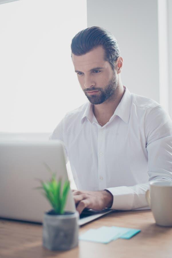 Sluit omhoog portret van de ernstige geconcentreerde knappe kalme ernstige mens die met laptop in bureau werken e-mail typen gebr stock fotografie
