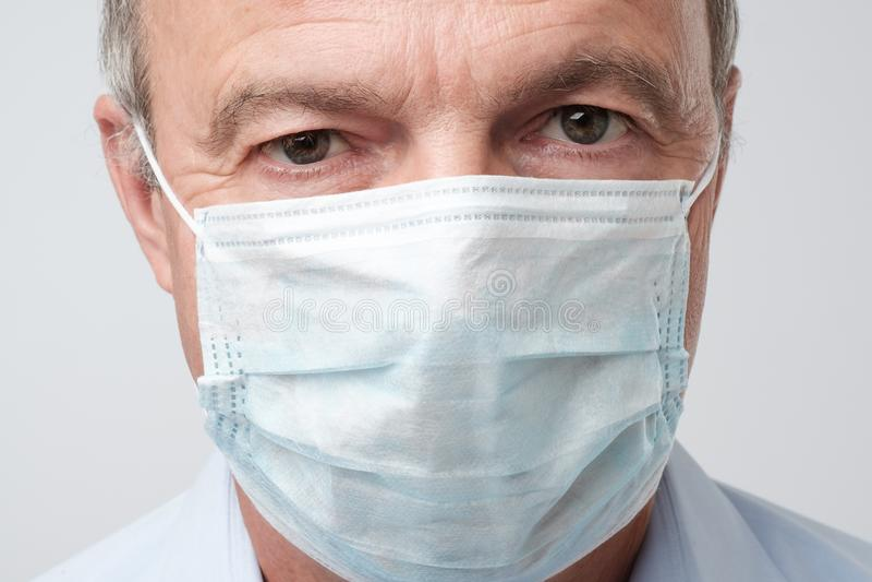 Sluit omhoog portret van de ernstige mens in speciaal doktersmasker Hij kijkt ernstig Rijpe ervaren arts stock foto
