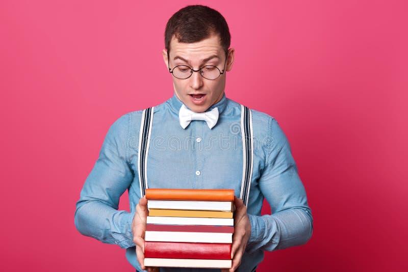 Sluit omhoog portret van de geinteresseerde verraste jonge mens die met schok dekking van hoogste boek bekijken, krantekop lezen  stock foto