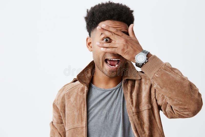 Sluit omhoog portret van de grappige mooie zwarte gevilde mens met afrokapsel in grijze t-shirt onder het bruine jasje kijken stock fotografie