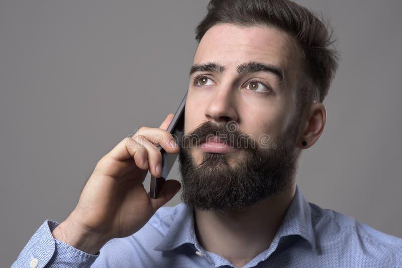 Sluit omhoog portret van de jonge gebaarde bedrijfsmens die op de mobiele telefoon spreken omhoog copyspace bekijken stock afbeelding
