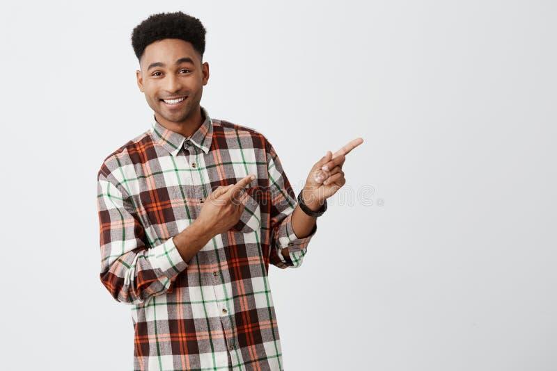 Sluit omhoog portret van de jonge knappe donker-gevilde mens die met modieus donker afrohaar in geruit overhemd glimlachen met royalty-vrije stock afbeelding