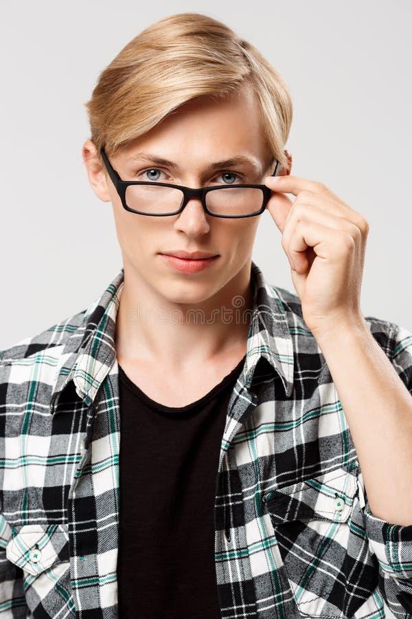 Sluit omhoog portret van de knappe blonde jonge mens die toevallig plaidoverhemd dragen kijkend in camera over glazen geïsoleerd  royalty-vrije stock fotografie