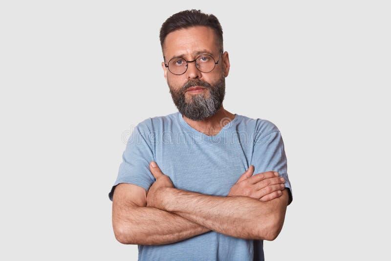 Sluit omhoog portret van de knappe mens met baard status met gevouwen wapens geïsoleerd op witte achtergrond, kijkt ernstig, toev royalty-vrije stock fotografie
