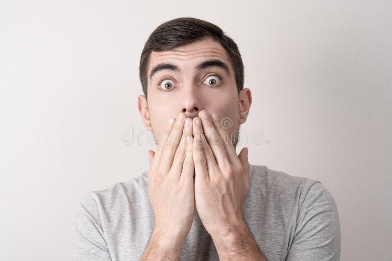 Sluit omhoog portret van de mens met geschokte gezichtsdekking zijn mond met zijn handen royalty-vrije stock foto