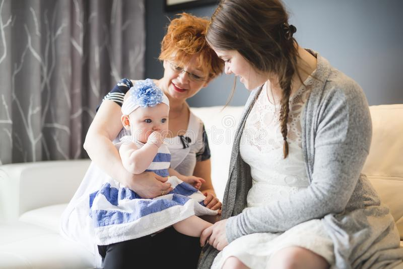 Sluit omhoog portret van drie generaties van vrouwen die dichte, grootmoeder, moeder en babydochter thuis zijn royalty-vrije stock fotografie