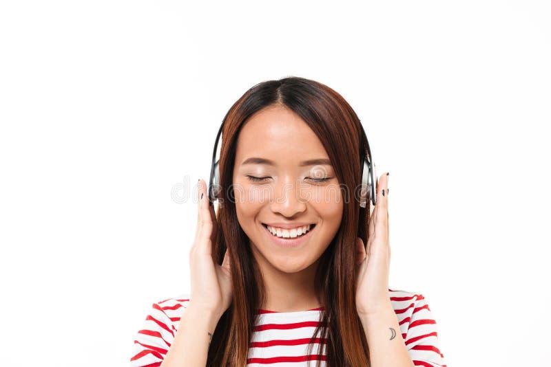 Sluit omhoog portret van een Aziatisch meisje die aan muziek luisteren royalty-vrije stock fotografie