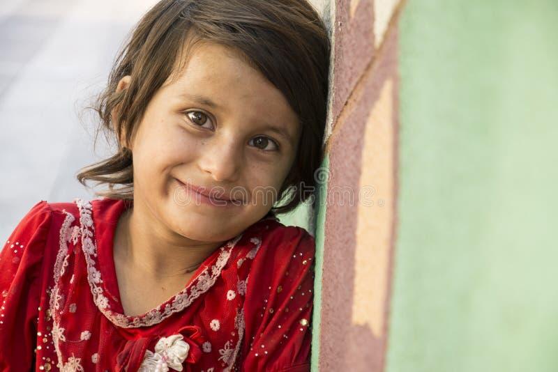 Sluit omhoog portret van een eenzaam meisje die klein weefsel verkopen stock foto