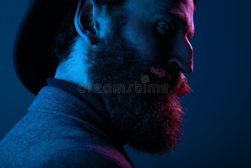 Sluit omhoog portret van een gebaarde mens in elegante hoed en kostuum, die in profiel in studio stellen, op blauwe achtergrond w royalty-vrije stock foto's
