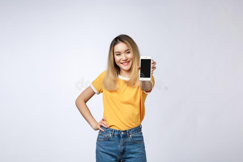 Sluit omhoog portret van een glimlachende Aziatische vrouw die het lege scherm mobiele telefoon tonen terwijl status geïsoleerd o royalty-vrije stock afbeelding