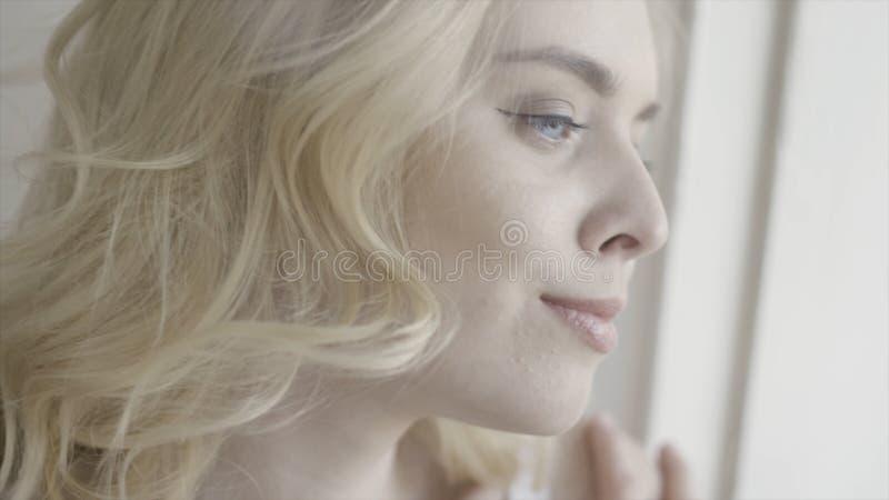 Sluit omhoog portret van een glimlachende blonde vrouw die buiten door venster kijken actie Mooi jong meisje met krullend haar royalty-vrije stock afbeelding