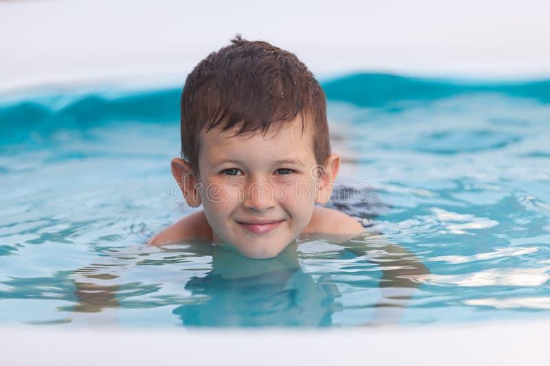 Sluit omhoog portret van een glimlachende jonge jongen in de pool Het concept van vakanties royalty-vrije stock foto