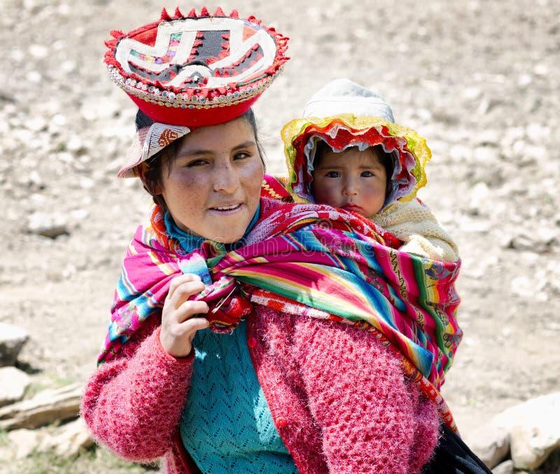 Sluit omhoog portret van een glimlachende Quechua vrouw gekleed in kleurrijke traditionele met de hand gemaakte uitrusting en het stock afbeelding