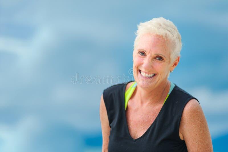 Sluit omhoog portret van een glimlachende rijpe oude vrouw met kort haar royalty-vrije stock afbeelding
