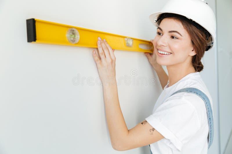 Sluit omhoog portret van een glimlachende vrouwenbouwer in bouwvakker stock fotografie